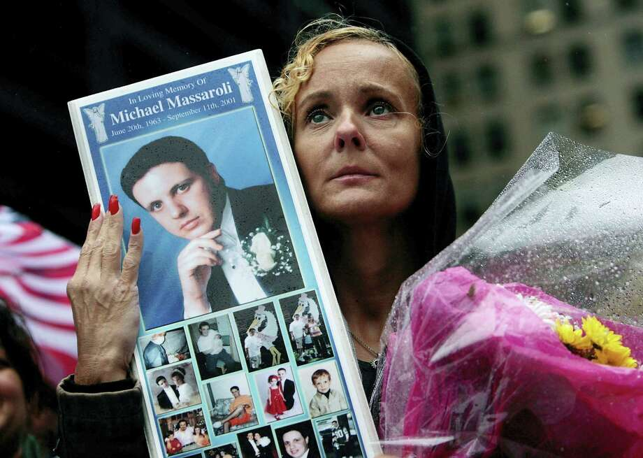 """FILE - In this Sept. 11, 2009 file photo, Diane Massaroli holds a picture of her late husband, Michael Massaroli, who worked as an investment executive in the World Trade Center, as his name is read during a ceremony at ground zero on eighth anniversary of the Sept. 11 terrorist attacks, in New York. Their son Michael is pursuing a career in public service because of the caring the public showed his family after his father was killed on 9/11. """"I really try and at least get positive personal growth out of something that was so horrific,"""" he says, """"rather than let it break me down."""" (AP Photo/Chris Hondros, Pool, File) Photo: AP / AP2009"""