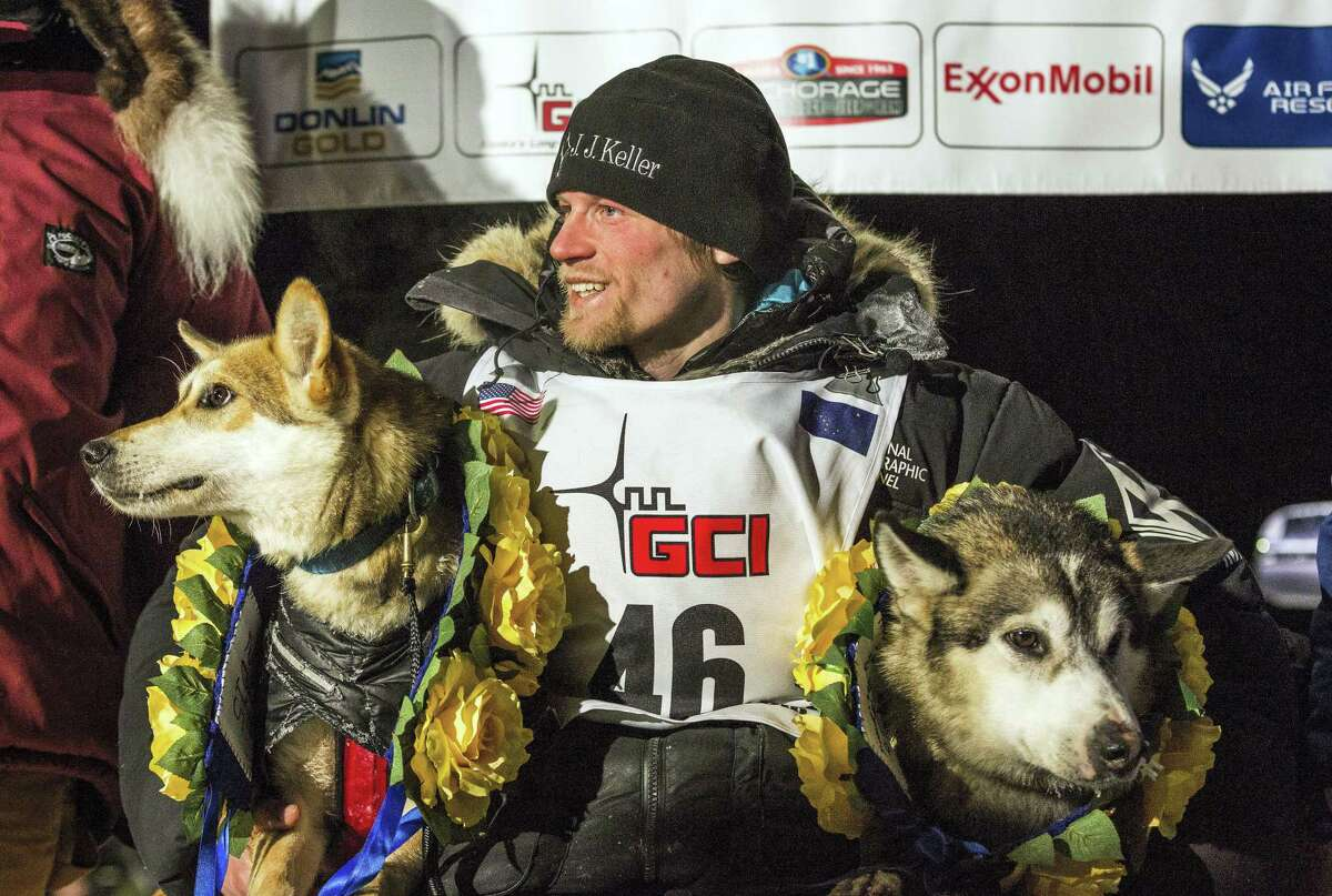 FILE - In this March 18, 2015, file photo, Dallas Seavey poses with his lead dogs Reef, left, and Hero in Nome, Alaska, after winning the Iditarod Trail Sled Dog Race. An absence of snow, a swan song for two-time champion Robert Sorlie or Norway and Dallas Seavey's bid for a fourth championship in the last five years highlight this year's Iditarod Trail Sled Dog Race. The world's most famous sled dog race starts Saturday in downtown Anchorage with a fan-friendly parade of mushers and their furry teams. (AP Photo/Alaska Dispatch News, Loren Holmes, File)