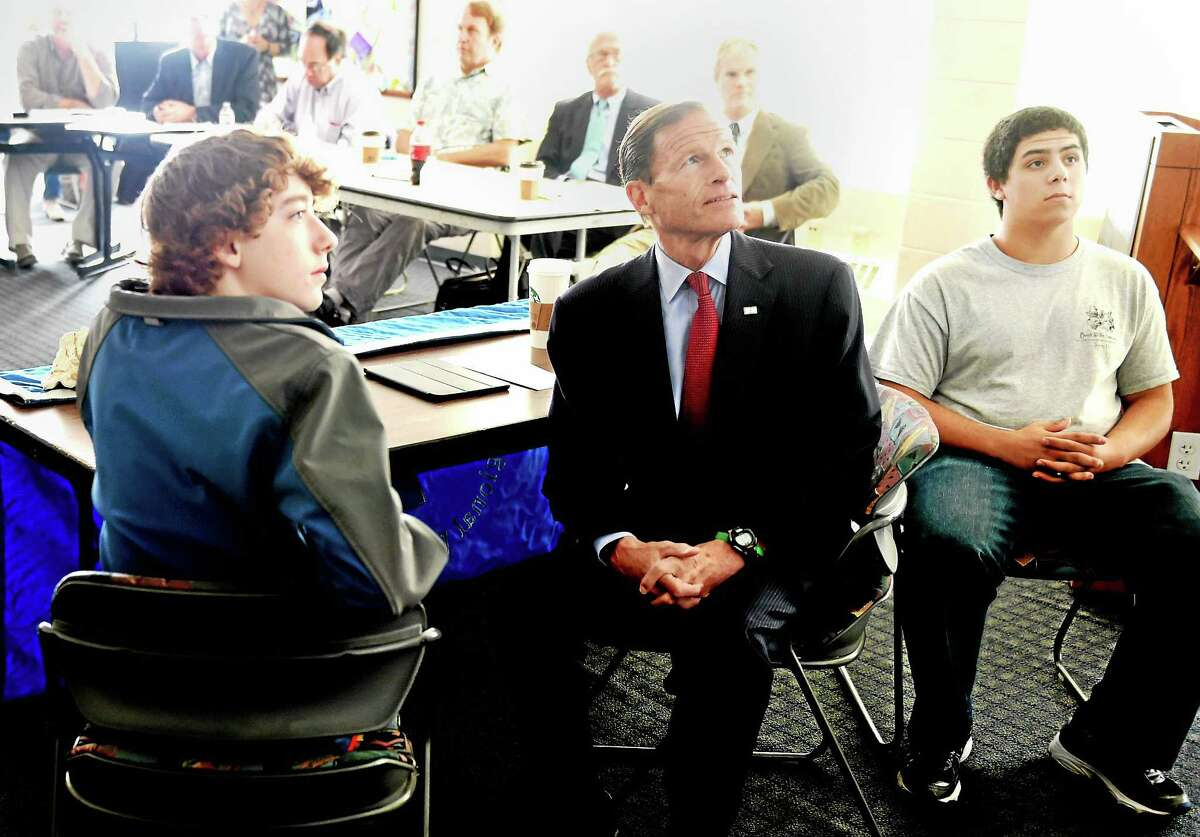 (Peter Hvizdak - New Haven Register)U.S. Senator Richard Blumenthal (D-CT), center, with Sound School Regional Vocational Aquaculture Center seniors Zachary Pope of Hamden, left, and Marcus Ramirez of North Haven, right, watch with other Sound School students, teachers, environmental groups and guests, a Connecticut Fund for the Environment and Save The Sound powerpoint presentation on the environmental and ecological significance of Plum Island Island during a public forum Tuesday, October 13, 2015 at the Sound School. The forum focused on efforts that are needed to protect the island from a Federal law requiring the sale of the island to the highest bidder.