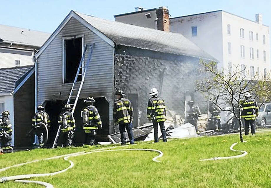 (Cassandra Day/Middletown Press)Middletown firefighters worked to put out a fire on Grand Street early Tuesday afternoon. The fire appeared to have damaged a garage and was under control shortly before 2 p.m. Photo: Journal Register Co.