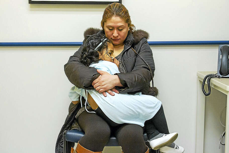 Karina Vasquez holds her daughter Angely Nunez as they wait for treatment at the Connecticut Children's Primary Care Center in Hartford. Tests revealed elevated levels of lead in Angely's blood and she began treatment with Dr. Hilda Slivka at the center. ( Photo by Tony Bacewicz / C-Hit.org) Photo: Journal Register Co. / C-Hit.org