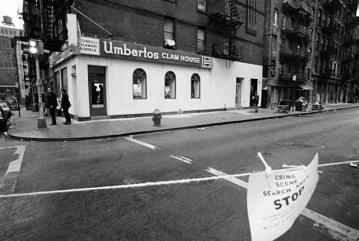 FILE - In this April 1972 file photo, police tape keeps pedestrians away from Umberto's Clam House after mobster Joey Gallo was was shot to death in the restaurant on Mulberry St., on his 43rd birthday, April 7, 1972, in New York's Little Italy neighborhood. Now an absence of fear in Little Italy reflects how a tourist destination with its shrinking cluster of Italian restaurants and gift shops has changed since the days when big name-gangsters claimed Mulberry Street as their turf. Visitors today would have a far better chance of dropping $400 on designer shoes than spotting an actual gangster. (AP Photo/Jerry Mosey, File)