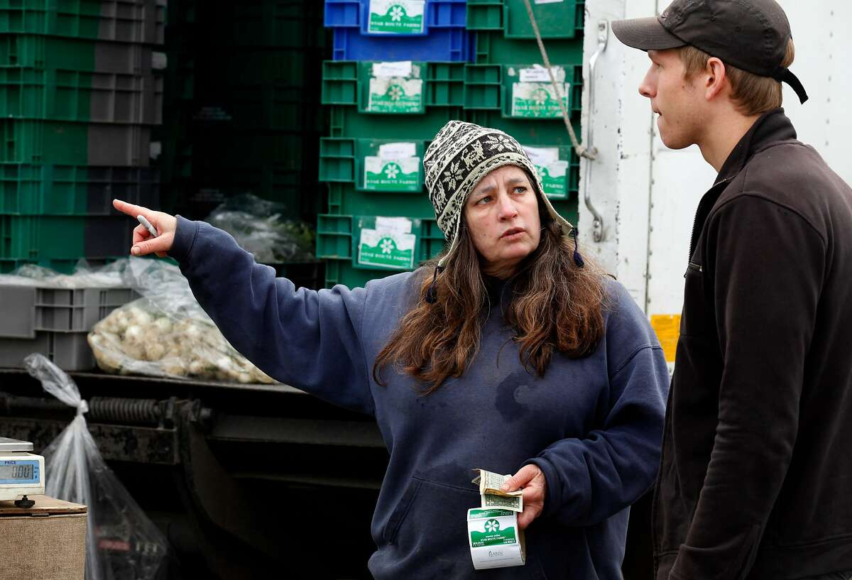 Annabelle Lenderink from Star Route Farms directs Brandon Rosen from Redd restaurant in Yountville CA to boxes of greens at Marin Farmers' Market Thursday, April 14, 2011.
