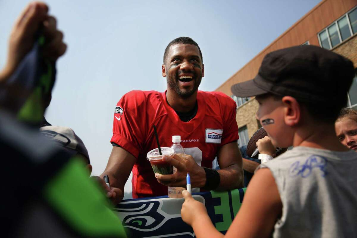 Russell Wilson signs autographs after Seahawks training camp, Monday, Aug. 7, 2017.
