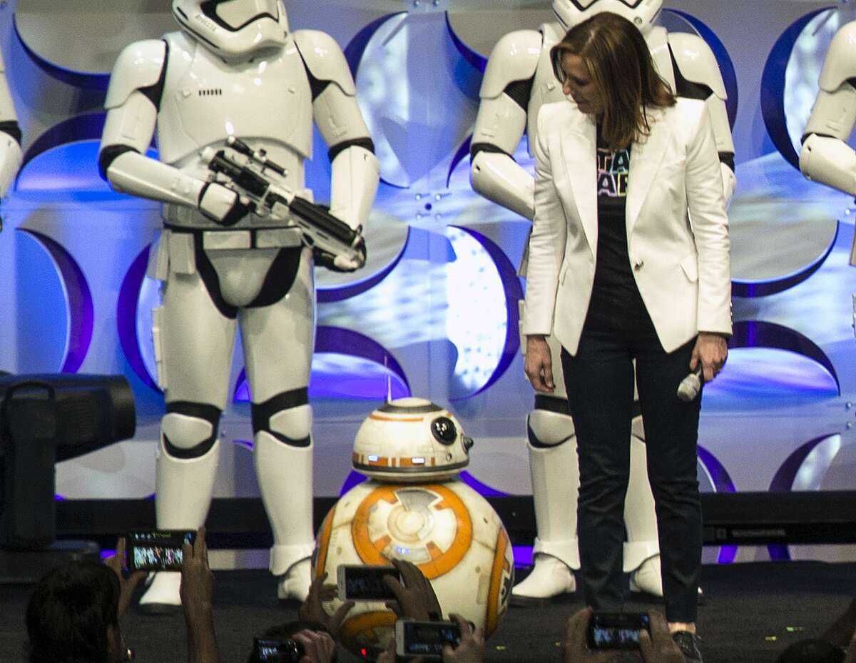 In this April 16, 2015 photo, producer Kathleen Kennedy, right, looks down at the BB-8 droid, featured in the upcoming film,