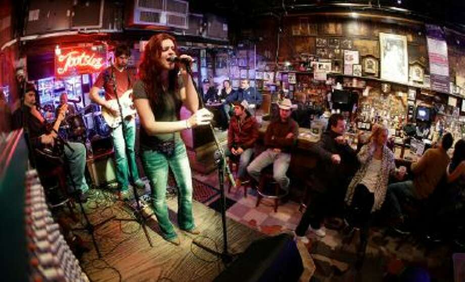 This Jan. 15, 2014 photo shows people listening to a band in Tootsie's Orchid Lounge in Nashville, Tenn. Tourists and locals flock to the row of honky tonks on lower Broadway.