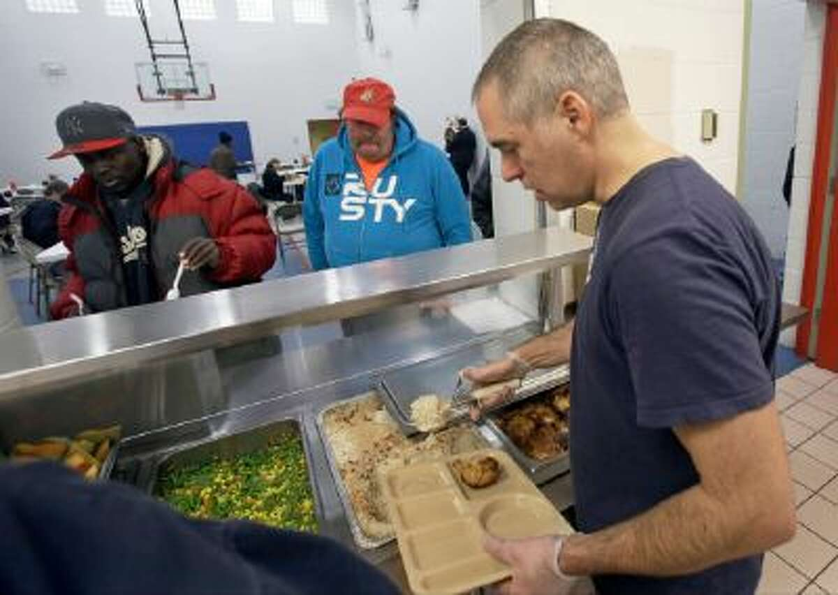 In this Nov. 14, 2013 photo, chef Jeff Ansorge serves up lunch at the Salvation Army Eastside Corp Community Center in St. Paul, Minn.