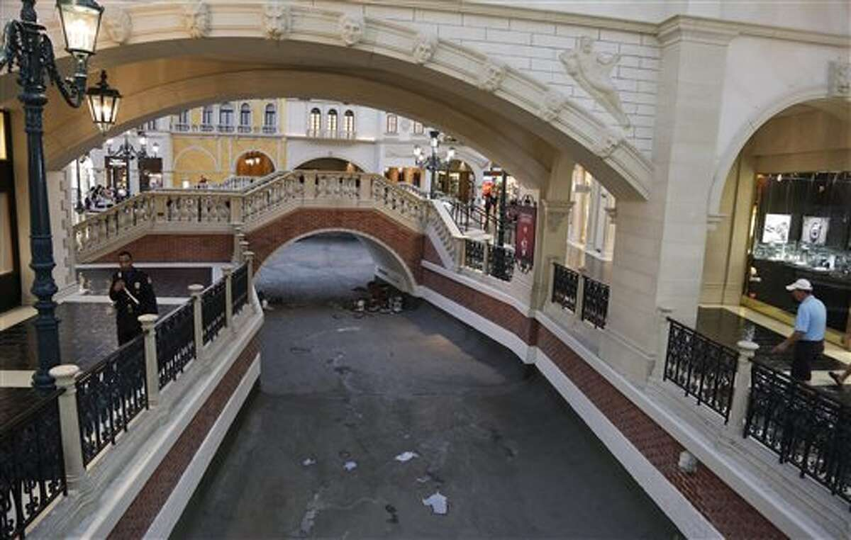 A security guard walks along the drained canal at the Venetian hotel-casino, Thursday, Sept. 19, 2013, in Las Vegas. Management has closed the waterways for several weeks for maintenance. (AP Photo/Julie Jacobson)