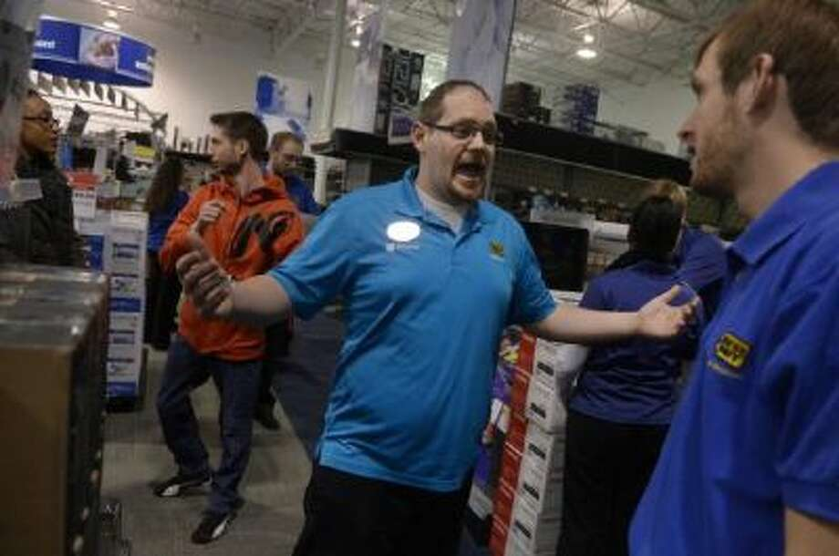 Employee Brent Gill poses a question while playing the part of a customer during a Black Friday rehearsal at a Best Buy store in Denver.