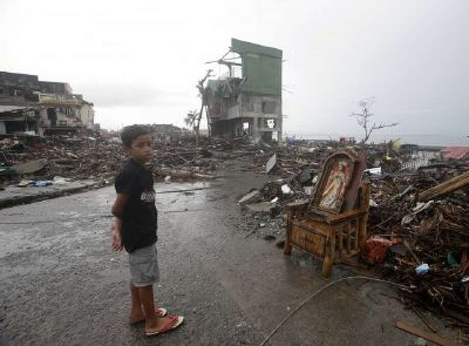 An icon of the Sacred Heart is placed on a chair amidst the rubble which were washed inland by typhoon Haiyan at Tacloban city.