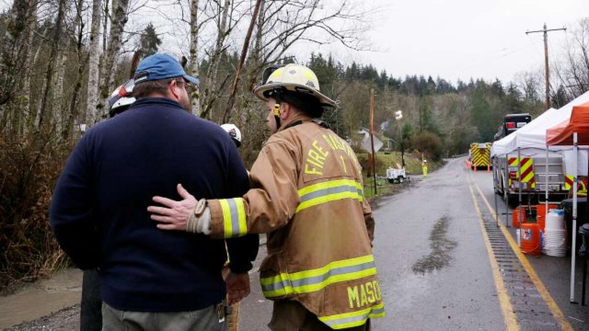 Snohomish County Fire Dept. Battalion Chief Steve Mason, right, briefly greets workers at the scene of a deadly mudslide Saturday, March 29, 2014, in Oso, Wash. Besides the more than two dozen bodies already found, many more people could be buried in the debris pile left from the mudslide one week ago. Ninety people are listed as missing. (AP Photo/Elaine Thompson, Pool)