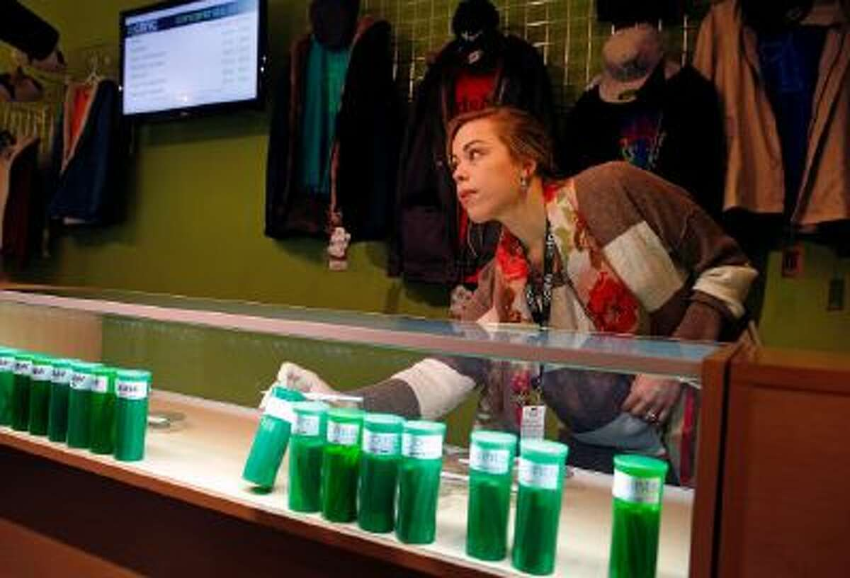 In this Dec. 6, 2013 photo, Elle Beau, an employee of The Clinic, a Denver-based dispensary with several outlets, reaches into a display case for marijuana while helping a customer, in Denver.