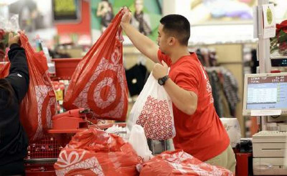 A Target employee hands bags to a customer at the register at a Target store in Colma, Calif., Friday, Nov. 23, 2012. Black Friday in 2012, the day when retailers traditionally turn a profit for the year.