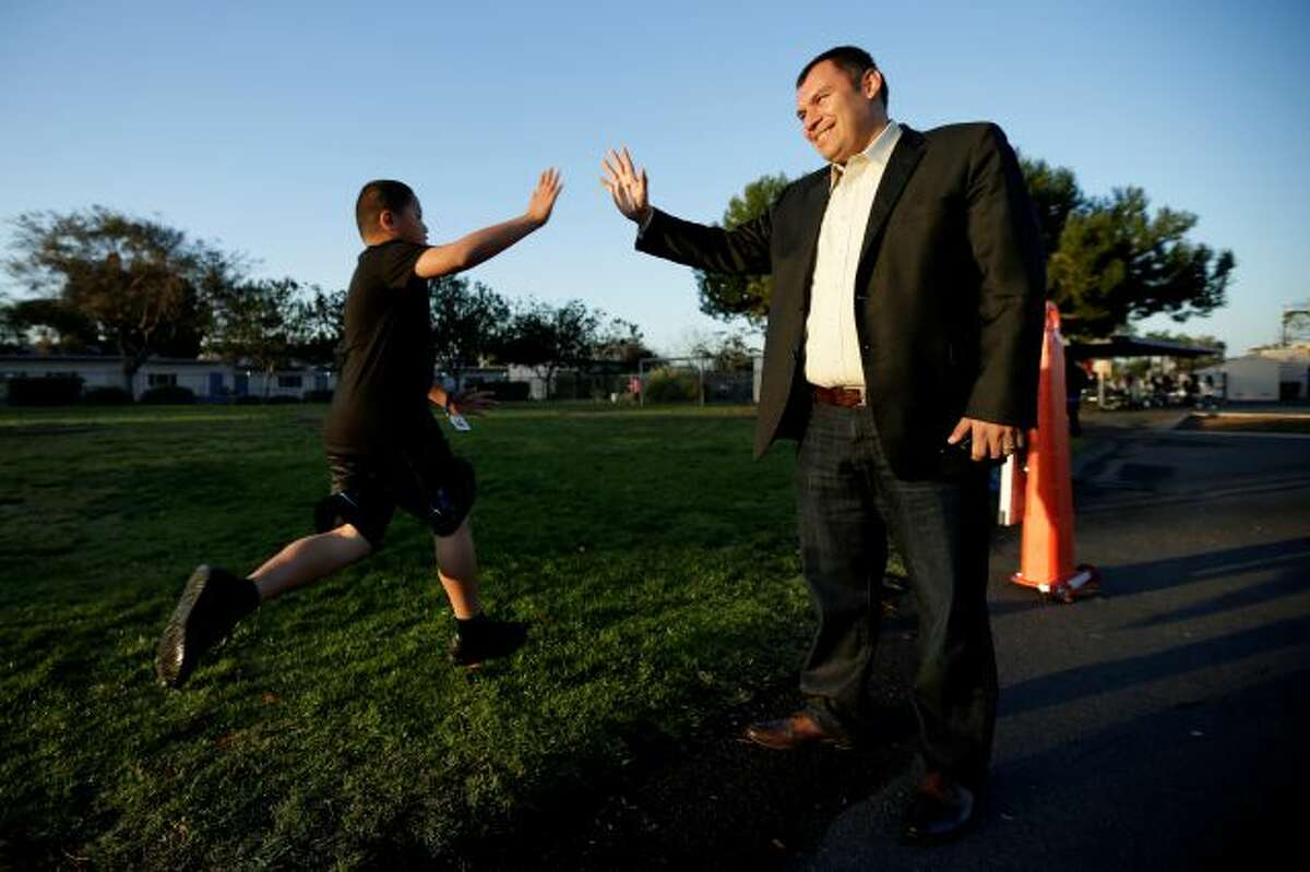 In this March 14, 2014 picture, Rice Elementary School Principal Ernesto Villanueva slaps hands with students during an early morning running program at an elementary school in Chula Vista, Calif. Amid alarming national statistics showing an epidemic in childhood obesity, hundreds of thousands of students across the country are being weighed and measured. Beltran son's Chula Vista Elementary School District is being touted as a model for its methods that have resulted in motivating the...