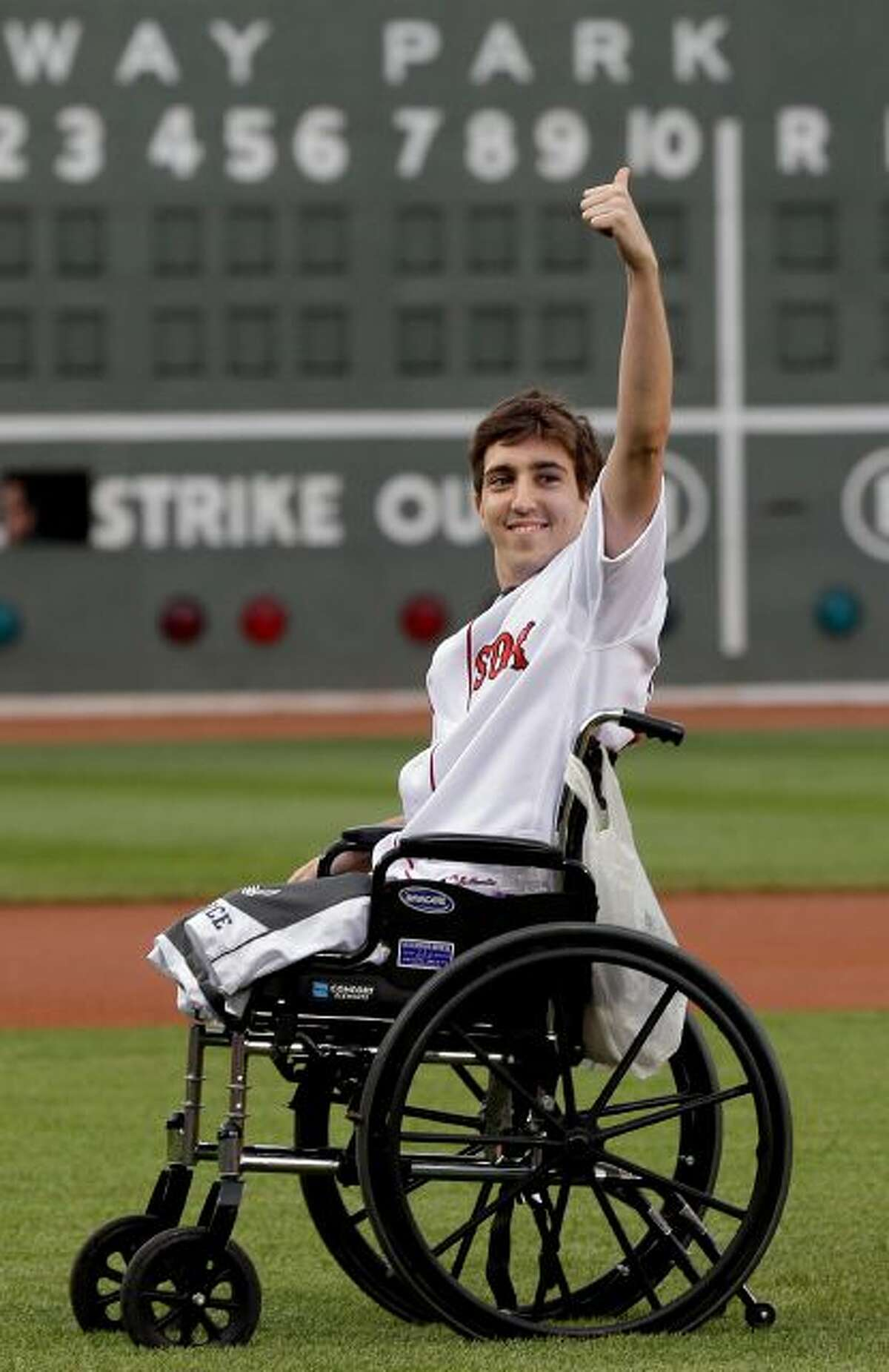 This May 28, 2013 file photo, Boston Marathon bombing survivor Jeff Bauman acknowledges cheering fans before throwing out a ceremonial first pitch at Fenway Park prior to a baseball between the Boston Red Sox and the Philadelphia Phillies in Boston. Bauman, who lost both legs in the Boston Marathon bombings, then helped authorities identify the suspects, is engaged and an expectant father. Bauman and his fiancé, Erin Hurley, tell The Associated Press that the baby is due July 14. They...