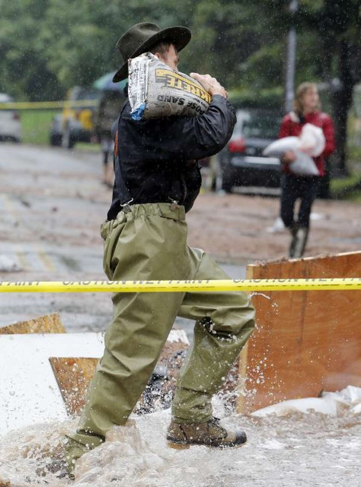 A man carries a sandbag through flood waters as residence of an apartment house work to divert flood water from their building in Boulder, Colo., on Thursday, Sept. 12, 2013. Flash flooding in Colorado has cut off access to towns, closed the University of Colorado in Boulder and left at least three people dead. (AP Photo/Ed Andrieski)