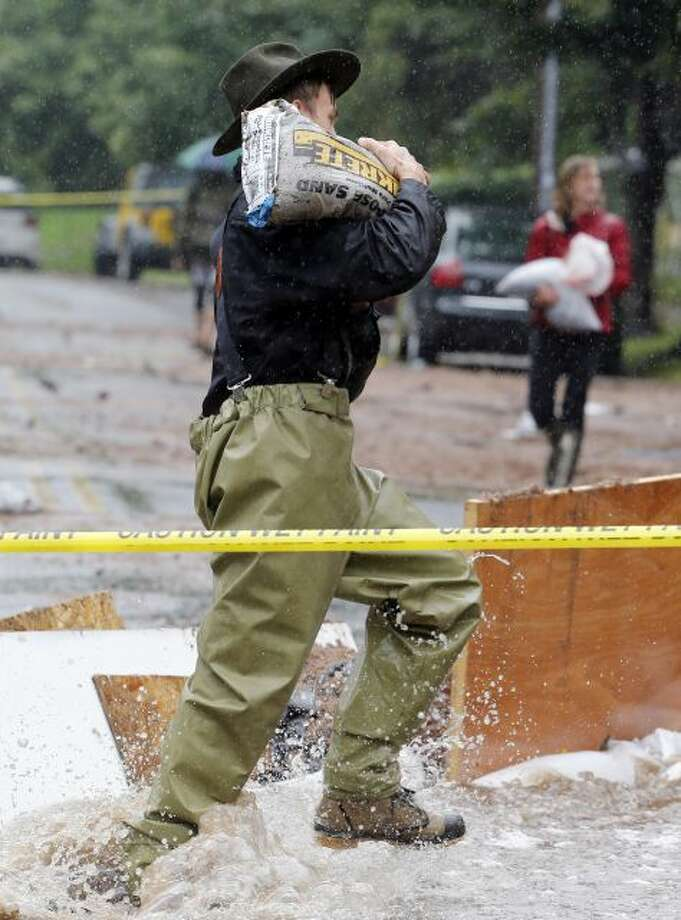 A man carries a sandbag through flood waters as residence of an apartment house work to divert flood water from their building in Boulder, Colo., on Thursday, Sept. 12, 2013. Flash flooding in Colorado has cut off access to towns, closed the University of Colorado in Boulder and left at least three people dead. (AP Photo/Ed Andrieski) Photo: AP / AP
