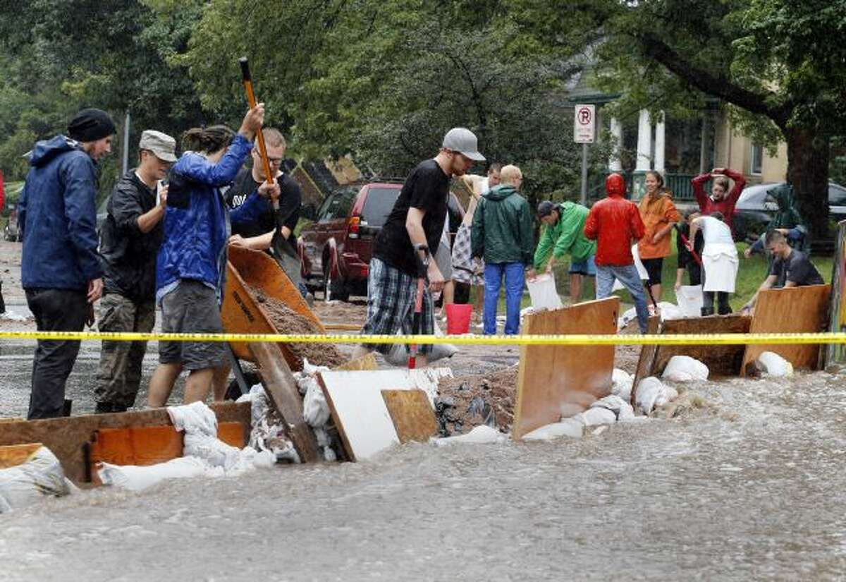 Residence of an apartment house work to divert flood water from their building in Boulder, Colo., on Thursday, Sept. 12, 2013. Flash flooding in Colorado has cut off access to towns, closed the University of Colorado in Boulder and left at least three people dead. (AP Photo/Ed Andrieski)