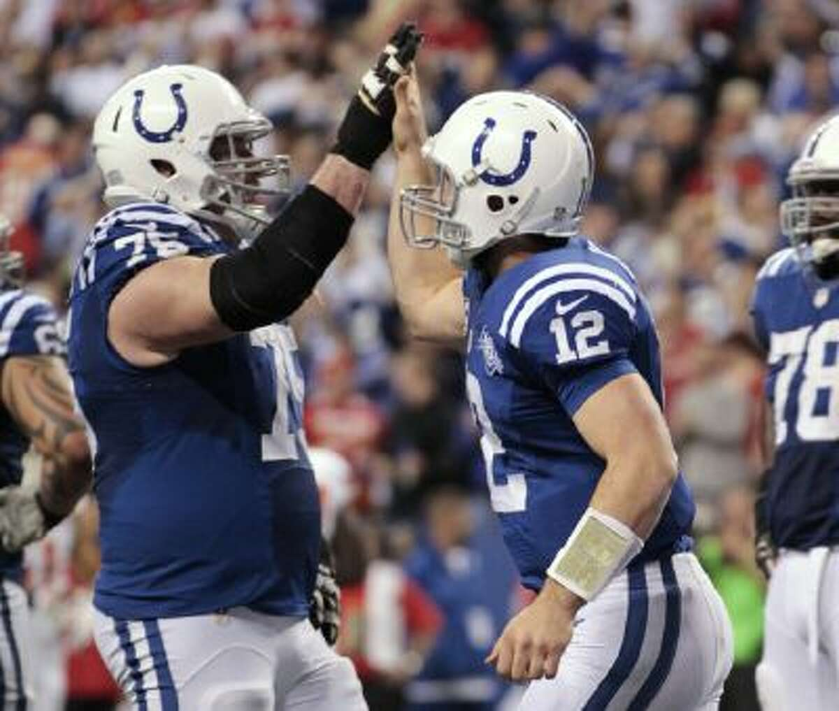 After scoring a touchdown against the Kansas City Chiefs, Indianapolis Colts quarterback Andrew Luck (12) celebrates with lineman Mike McGlynn (75).