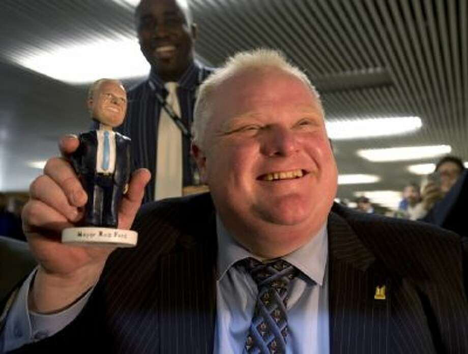 In this Tuesday, Nov. 12, 2013 file photo, Toronto Mayor Rob Ford holds a bobblehead doll depicting him at Toronto City Hall.