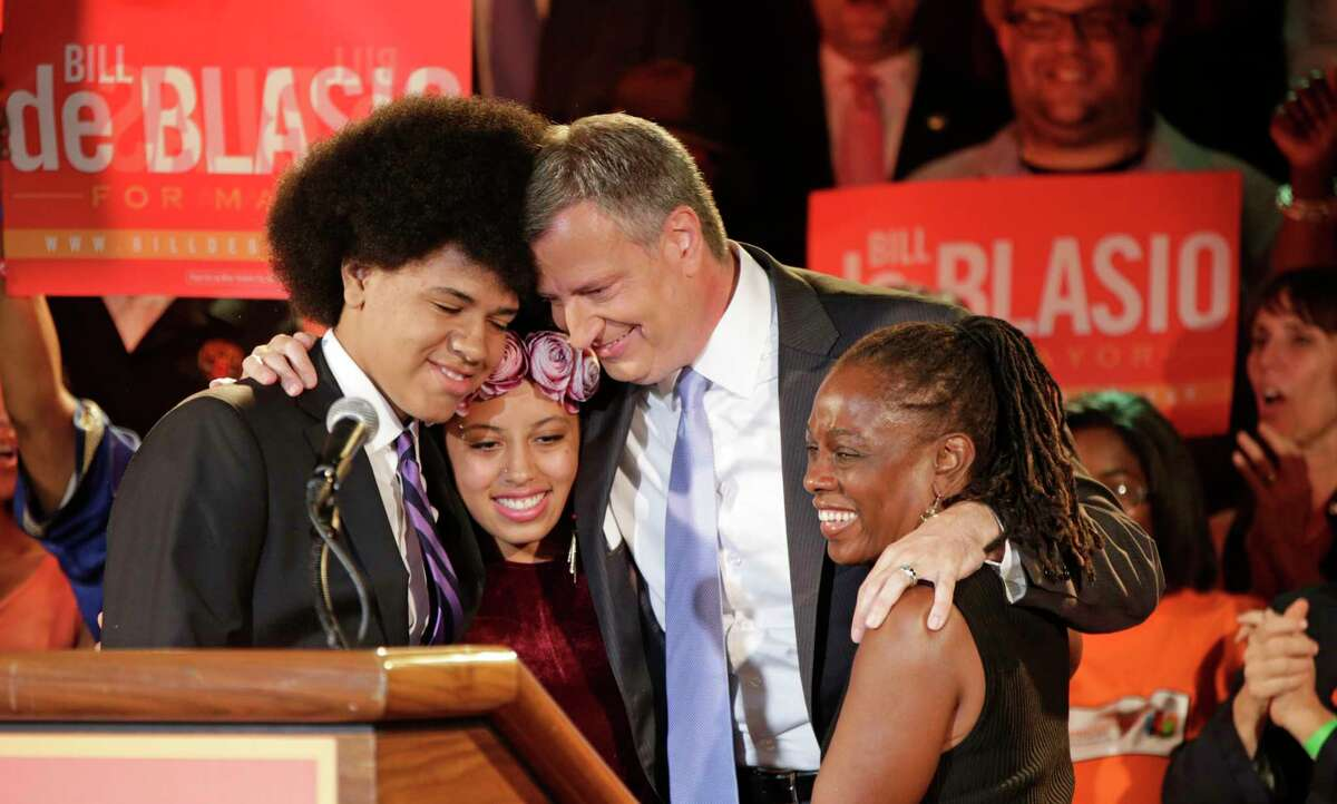 New York City Democratic mayoral hopeful Bill de Blasio embraces his son Dante, left, daughter Chiara, second from left, and wife Chirlane McCray, right, at his election headquarters after polls closed in the city's primary election Tuesday, Sept. 10, 2013, in New York. (AP Photo/Kathy Willens)