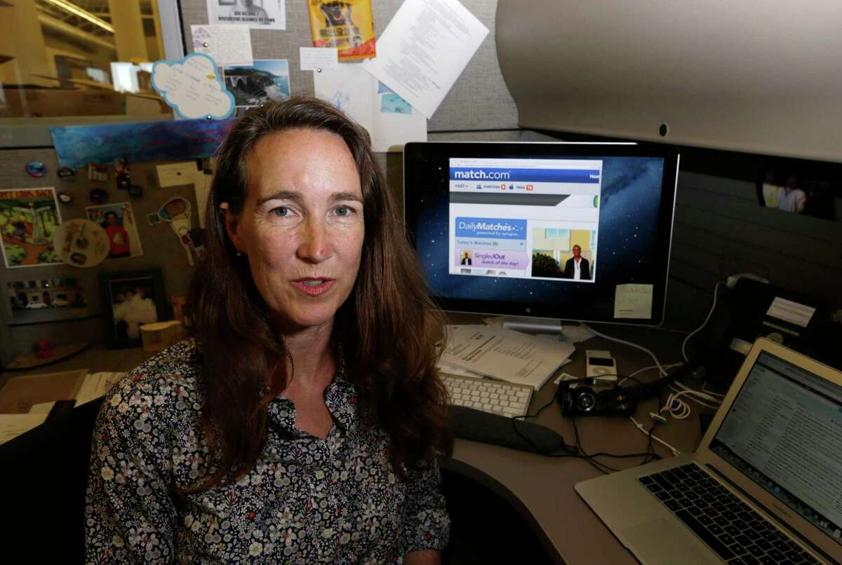 Lynn Boyden, an information architect in web services at the University of Southern California, poses with a dating website on her computer at the USC information technology services center in Los Angeles Wednesday, Sept. 4, 2013. Boyden says she has developed two identities online: a public one for her professional life and a private one that only a few close friends can access. She tries to block advertising trackers when she can and limits what personal data might wind up on public sites. (AP Photo/Reed Saxon)