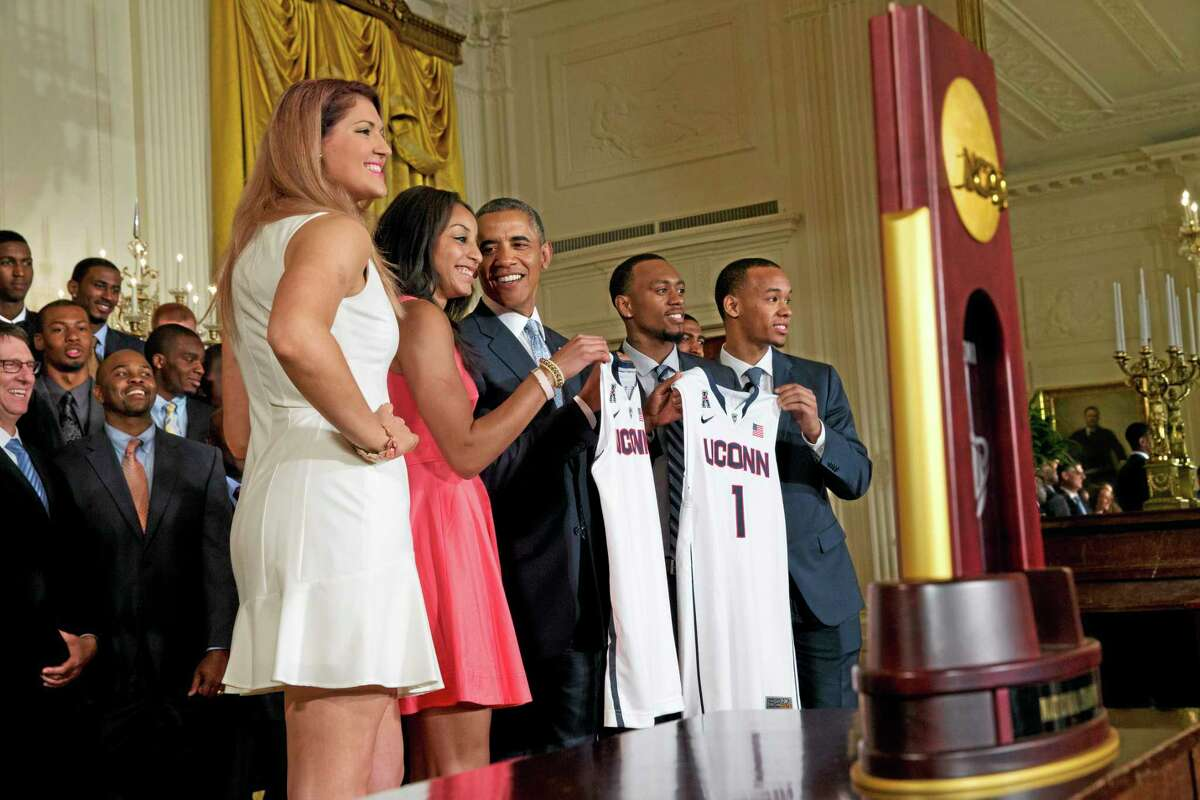 Stefanie Dolson, left, and Bria Hartley, and men's players Ryan Boatright, and Shabazz Napier, give jerseys to President Barack Obama.