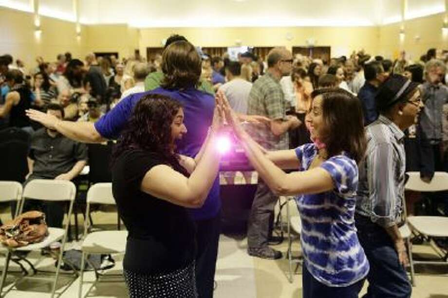 Attendees play a game with each other at the Sunday Assembly, a godless congregation founded by British comedians Sanderson Jones and Pippa Evans, on Sunday, Nov. 10, 2013, in Los Angeles.