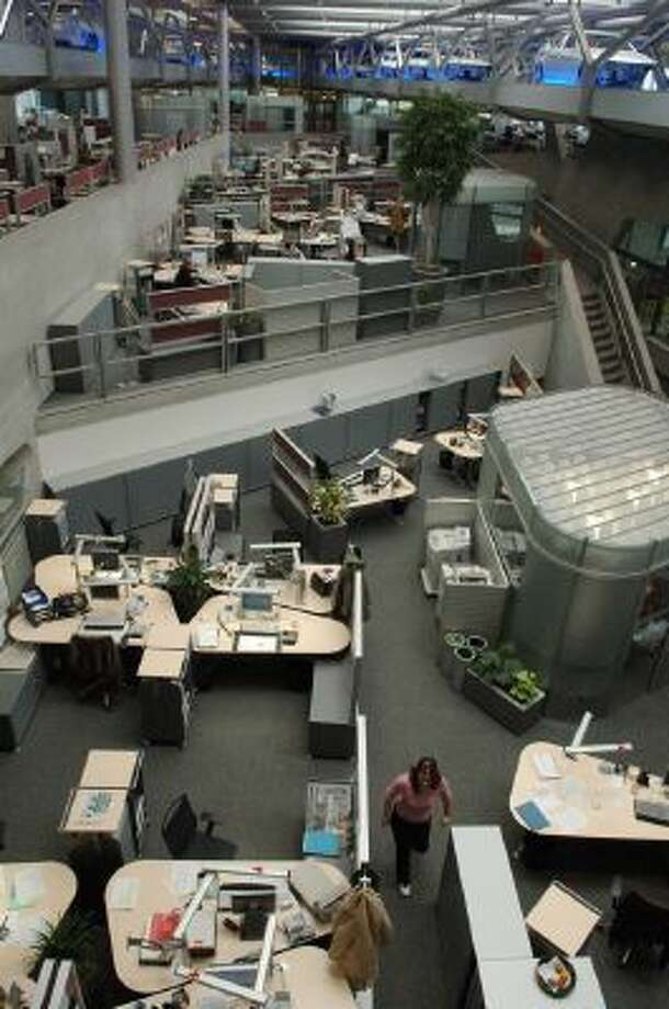Like Detroit, Leipzig was an industrial center that shriveled losing 20 percent of is population after reunification. Now it's Germany's fastest-growing city, with help from jobs at BMW and Porsche. Shown, an employee walking among desks as BMW 3-series coupe automobile chassis glide above at the BMW factory in 2006 designed by noted architect Zaha Hadid.