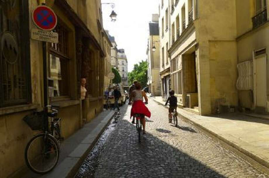 In Paris, bicyclists ride on a narrow street. Paris is one of the friendliest bicycling cities the author ever pedaled.