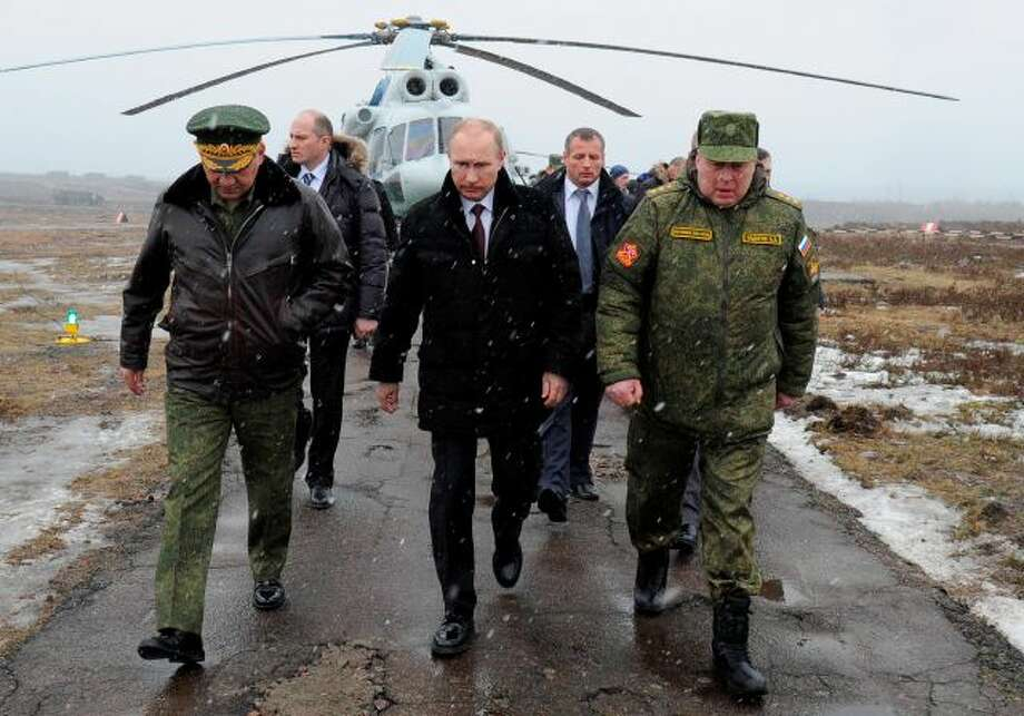 Russian President Vladimir Putin, center, and Defense Minister Sergei Shoigu, left, and the commander of the Western Military District Anatoly Sidorov, right, walk upon arrival to watch military exercise near St.Petersburg, Russia, Monday, March 3, 2014. Putin has sought and quickly got the Russian parliament's permission to use the Russian military in Ukraine.(AP Photo/RIA-Novosti, Mikhail Klimentyev, Presidential Press Service) Photo: AP / RIA Novosti Kremlin Press Service