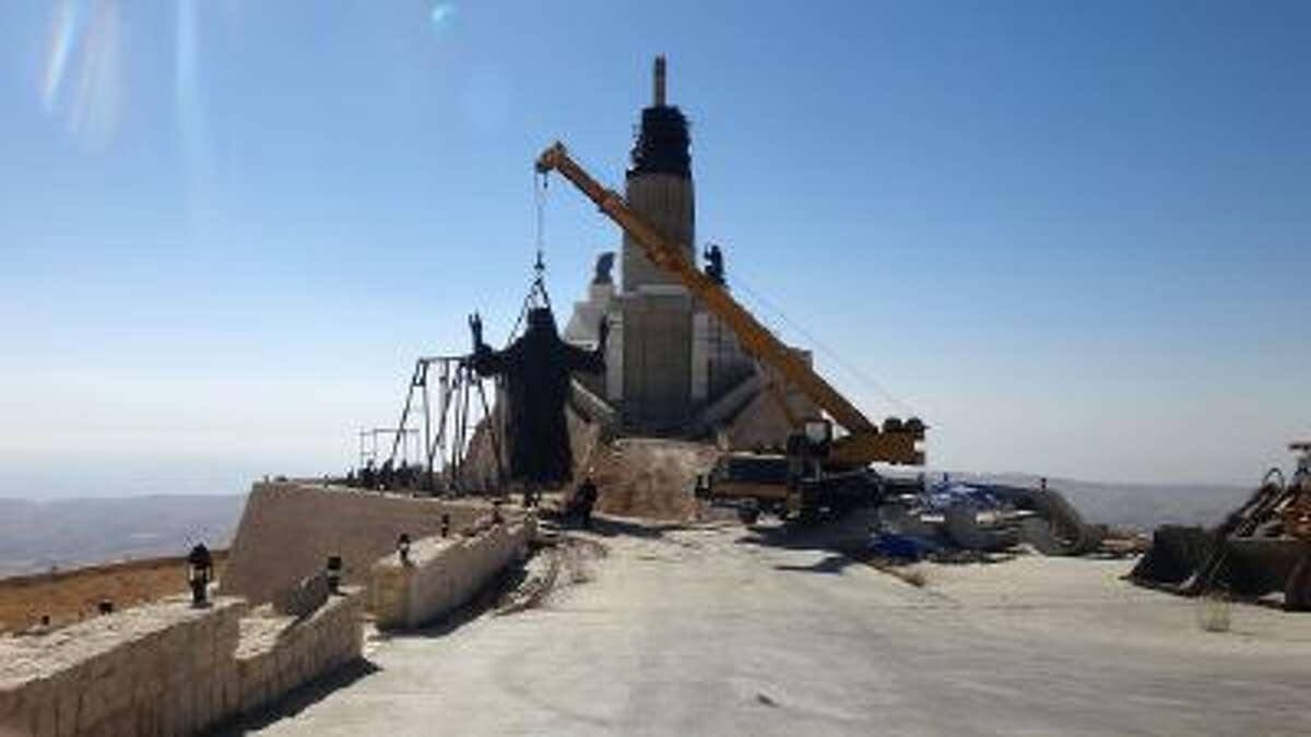 his Oct. 14, 2013 photo provided by the St. Paul's and St. George's Foundation shows workers preparing to install a statue of Jesus on Mount Sednaya, Syria.