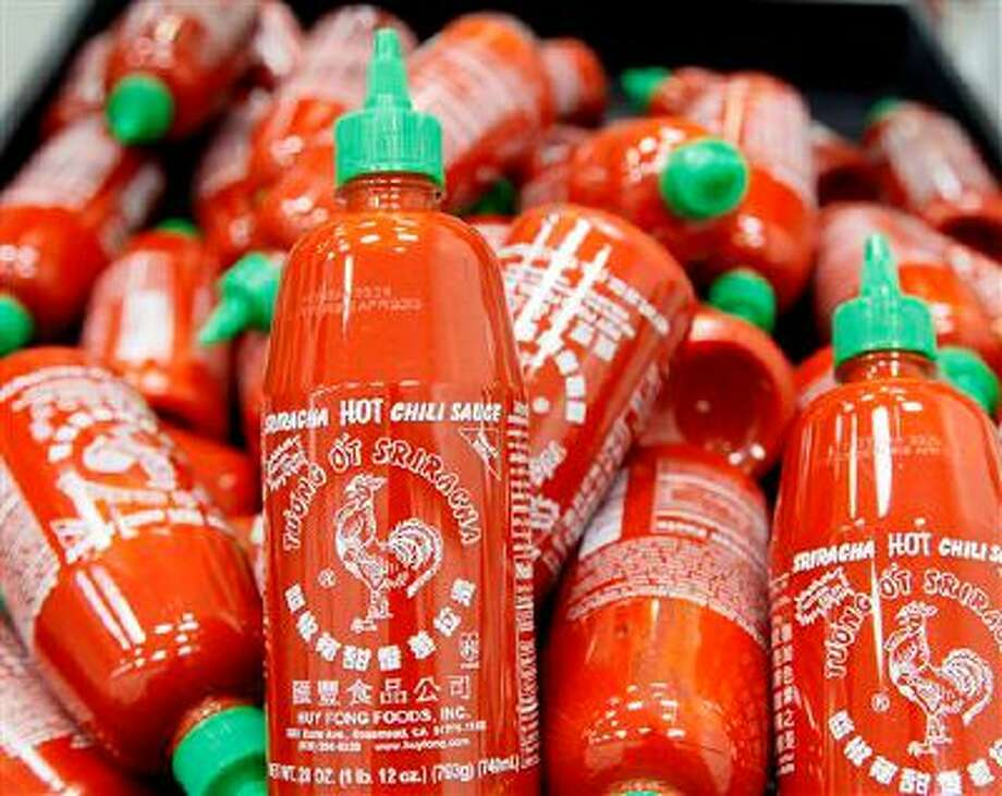 Sriracha chili sauce bottles are produced at the Huy Fong Foods factory in Irwindale, Calif., on Tuesday, Oct 29, 2013. The maker of Sriracha hot sauce is under fire for allegedly fouling the air around its Southern California production site. The city of Irwindale filed a lawsuit in Los Angeles Superior Court Monday asking a judge to stop production at the Huy Fong Foods factory, claiming the chili odor emanating from the facility is a public nuisance. (AP Photo/Nick Ut) Photo: AP / AP