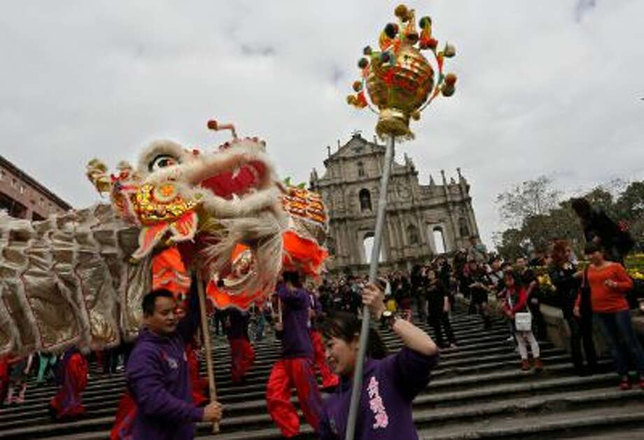 In this Feb. 1, 2014 photo, local artists perform dragon at the famous tourist spot the Ruins of St. Paul's during a Chinese New Year celebration in Macau.