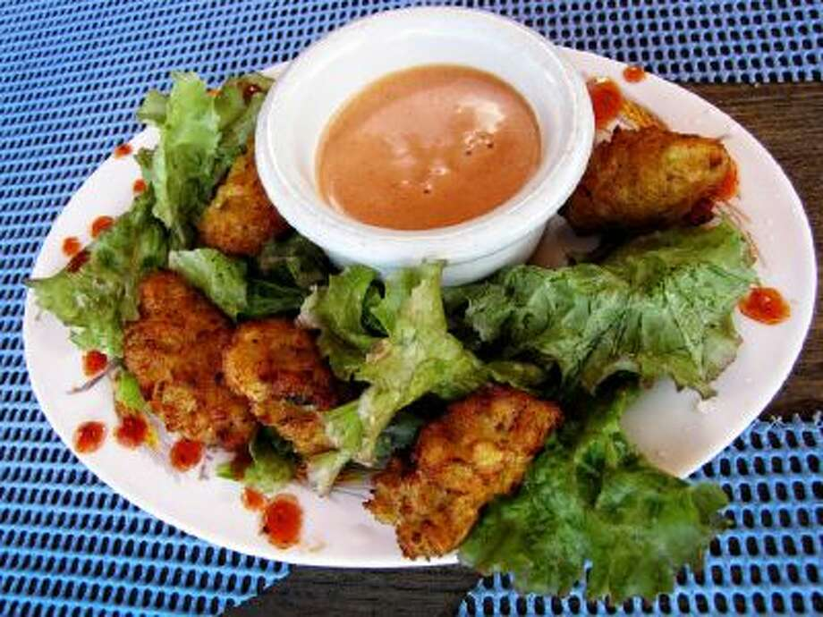 Conch fritters with a side of special hot sauce is served at the popular beachfront hangout, Sunshine's Beach Bar and Grill in Nevis.