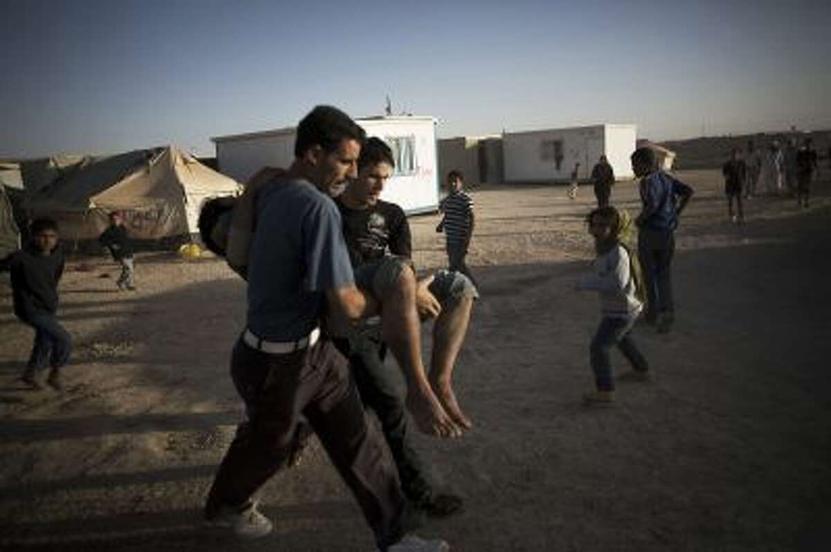 In this Tuesday, Oct. 22, 2013, photo, Syrian refugees carry a man who was wounded by a gas explosion during a fire at the Zaatari refugee camp near the Syrian border in Jordan. With Syria's civil war in its third year, more than 2 million Syrians have fled their country. About 100,000 live in this camp. (AP Photo/Manu Brabo)