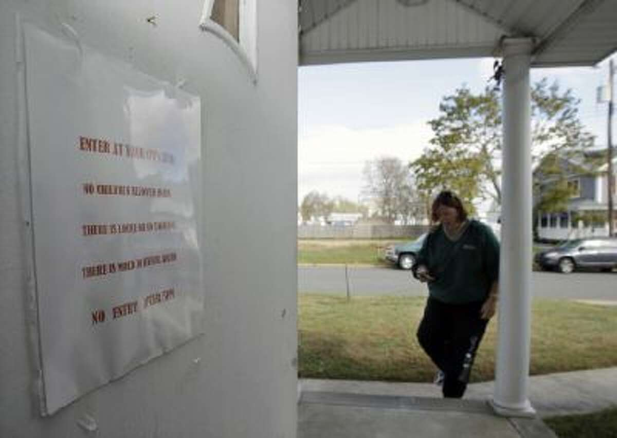 A warning sign is seen on the door of the Superstorm Sandy damaged home of Lee Ann Newland near the Shark River in Neptune, N.J., Sunday, Oct. 13, 2013.