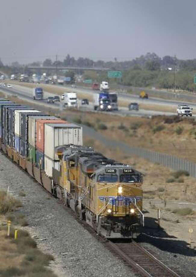 In this photo taken Thursday, Oct. 10, 2013, a freight train travels south alongside Highway 99 near Livingston, Calif.