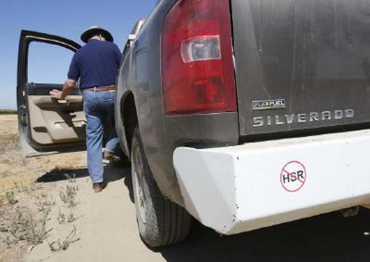 In this photo taken Tuesday, July 16, 2013, farmer Kole Upton climbs into his pickup which bears a sticker showing his opposition to the proposed high-speed rail system, at his ranch in Chowchilla, Calif.