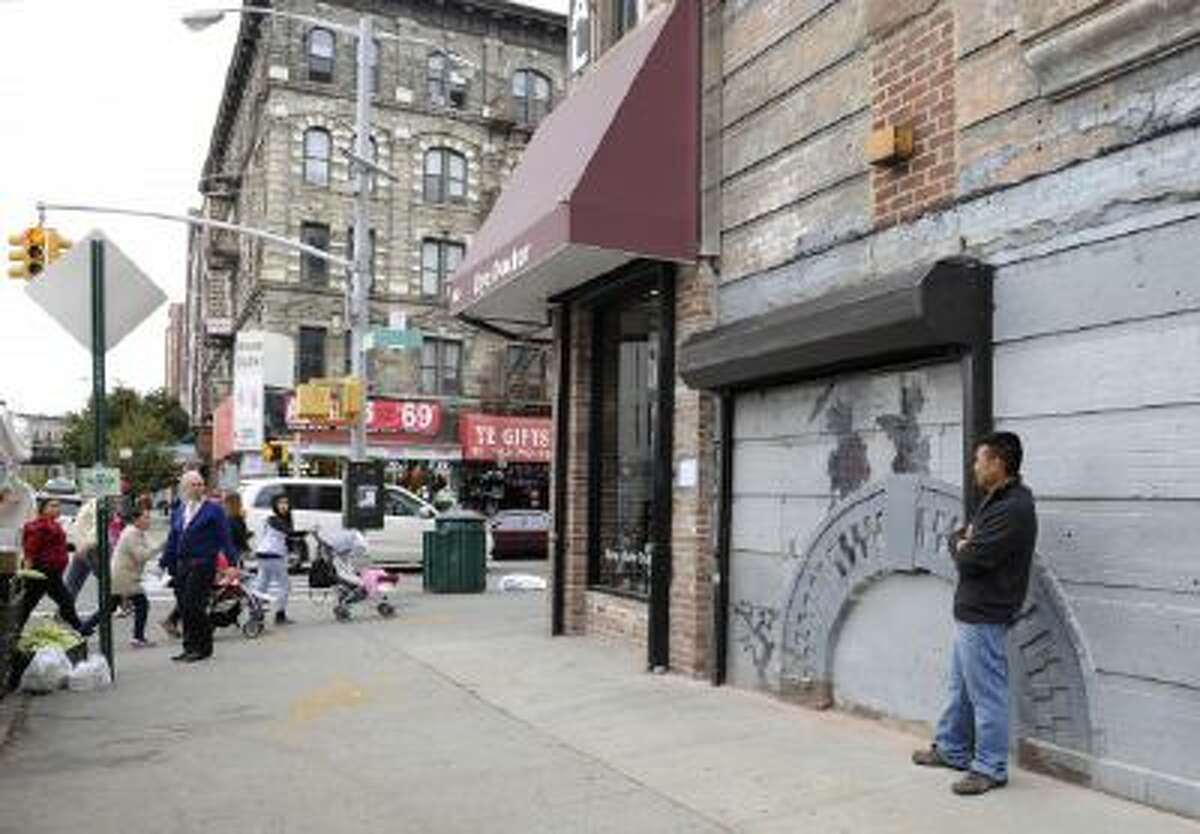 Feliciano Perez guards the work by British graffiti artist Banksy on Saturday, Oct. 19, 2013, in the Brooklyn borough of New York.