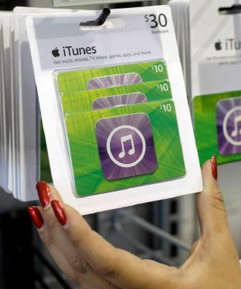 Customer picks up an Apple iTunes gift card on display at a Best Buy in Mountain View, Calif.