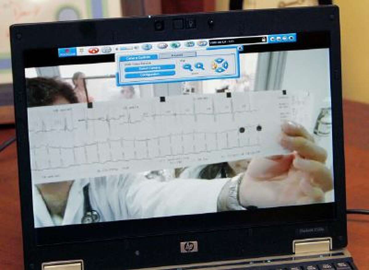 Dr. Gaston Castillo holds an EKG readout for the camera during a telemedicine hookup with Dr. Ricardo Munoz at Childrens Hospital of Pittsburgh.