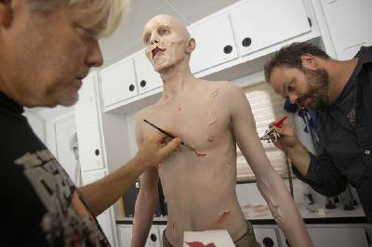 In this photo taken Friday, Oct 7, 2012, Kevin Galbraith, 24 of Marietta, Ga., undergoes a three hour make-up session to transform into his zombie character with the help of effects make-up artists Andy Schoneberg, right, and Kevin Wasner, left, on the set of AMC's television show, ?The Walking Dead,? in Senoia, Ga.