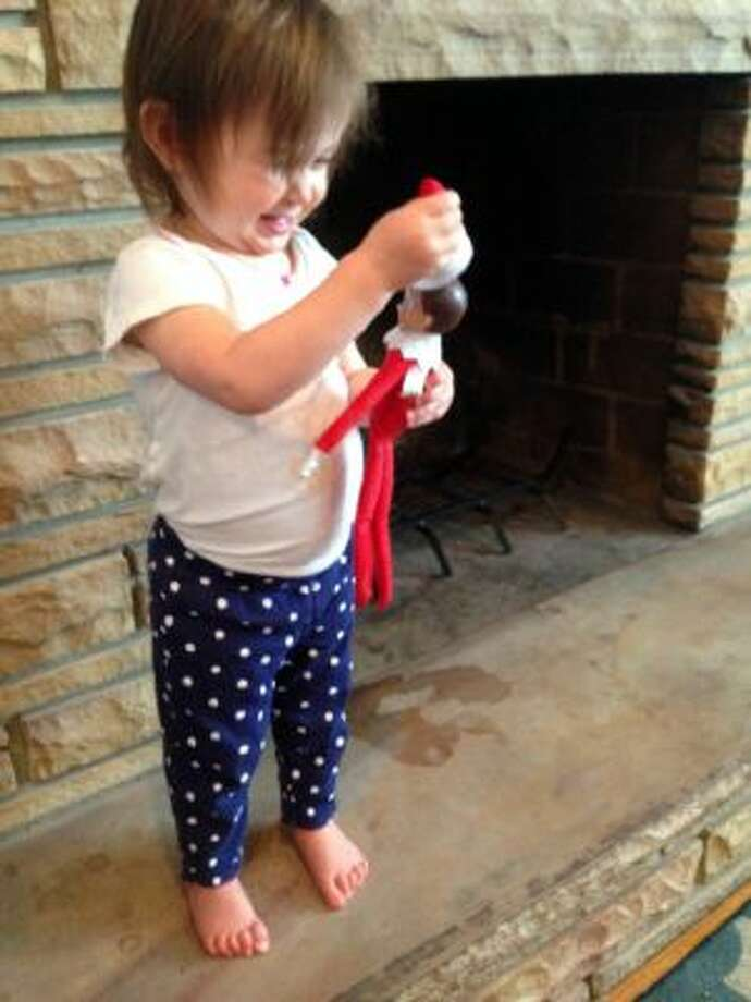 This Dec. 4, 2013 image released by Carly Kerby shows her 18 month-old daughter Mati playing with a felt elf at their home in Salt Lake City, Utah.