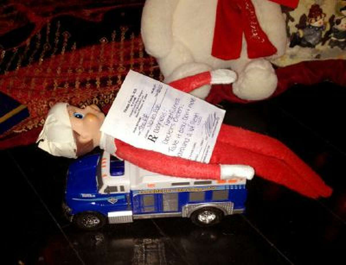 This Dec 11, 2013 photo released by Kim Boerman shows a bandaged elf from the Elf on the Shelf with a prescription by the Christmas tree in the Boerman home in Charleston, S.C. Boerman procured a doctor's prescription after the elf fell from the chandelier during dinner.