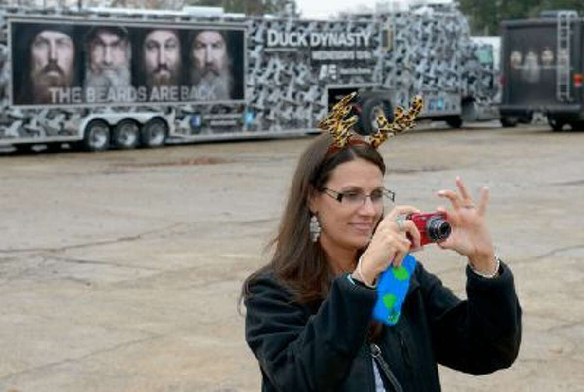 This Dec. 21, 2013 photo shows Trish Singlteon, of Durant, Okla., taking a picture of her family outside the Duck Commander store in West Monroe, La.