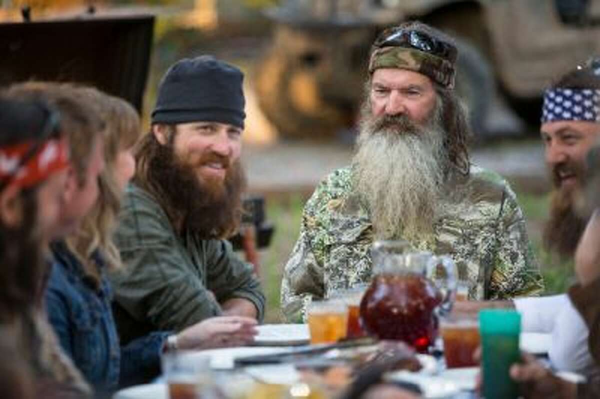This undated image released by A&E shows Phil Robertson, flanked by his sons Jase Robertson, left, and Willie Robertson from the popular series