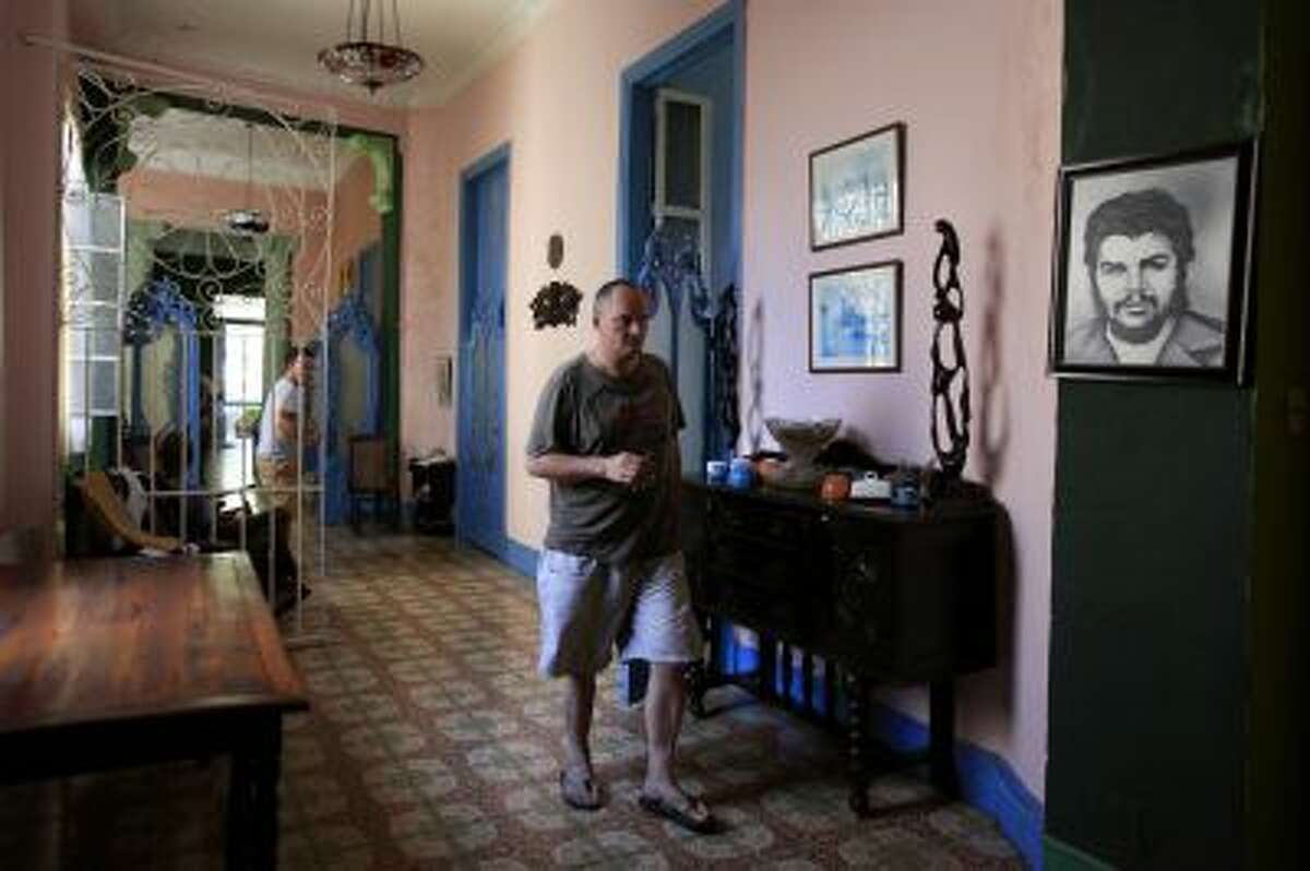 In this Oct 13, 2013 photo, German tourist Thomas David Knock walks through a corridor of a rental house in Havana, Cuba. Some 436,000 Cubans are running or working for private small businesses under President Raul Castro's package of social and economic reforms begun in 2010. Among other things, the government has legalized used car and real estate sales and ended the much-detested exit visa required for decades of all islanders seeking to travel overseas. (AP Photo/Franklin Reyes)