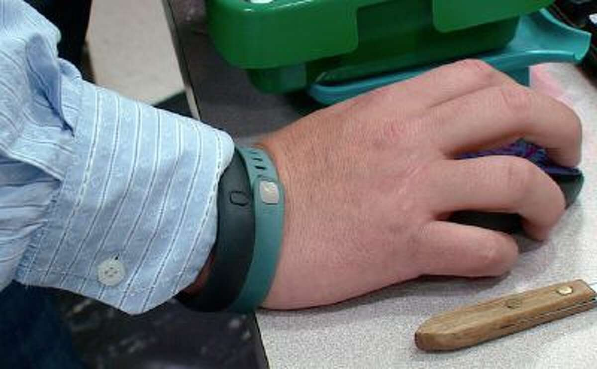 This photo from video taken Oct. 9, 2013 shows the wrist of Tim Davis wearing his FitBit, green, and Nike FuelBand, black, devices he uses to track his physical activity and habits, in New Brighton, Pa.
