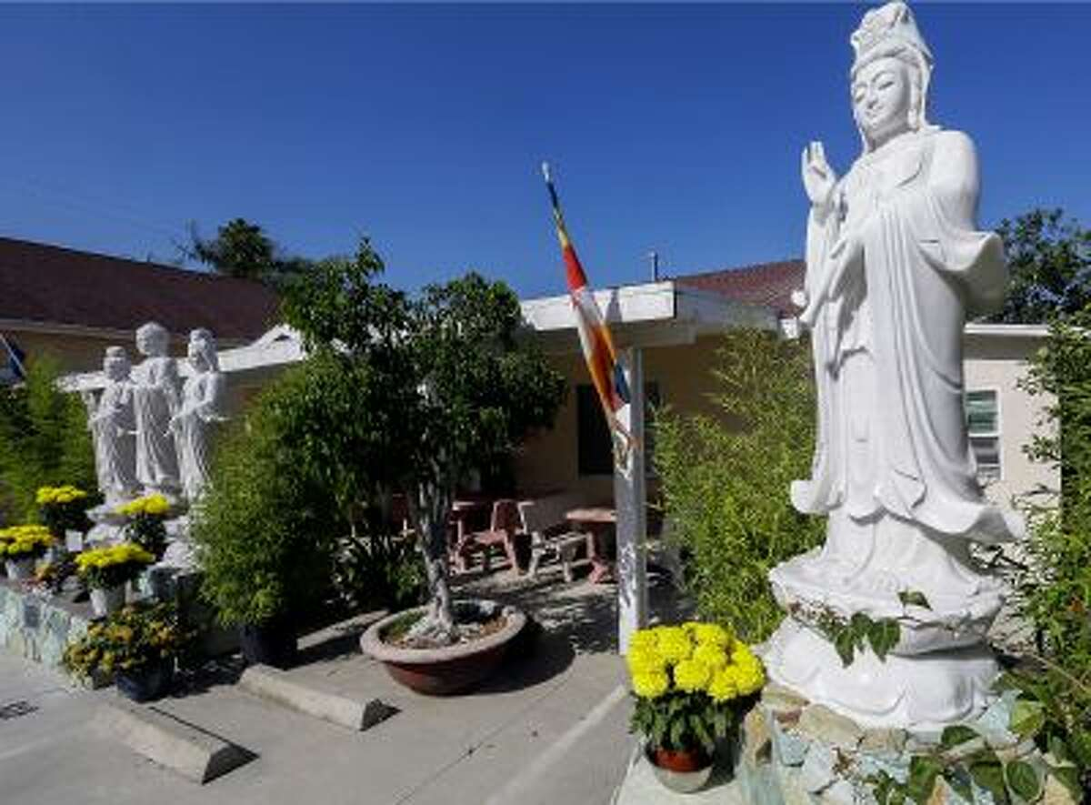 In this Sept. 18, 2013 photo, Buddhist statues decorate the entrance to the Lu Mountain Temple in Rosemead, Calif. The temple has become a repository for the colorful crystals and a tooth and a hair that are believed to have come from the body of the Buddha himself.